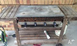 A 4 burner gas BBQ with a teak stand with wheels. Very