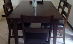 Dining chairs feature solid, dark timber legs, a high