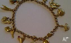 This 9ct yellow gold charm bracelet has 13 gorgeous 9ct