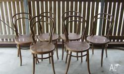 A set of 6 matching antique cafe wicker dining chairs.