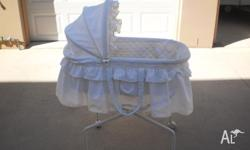 White baby bassinet with broderie anglise linen and