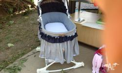 Blue hooded bassinet. Rocks and (wheels around) rolls.
