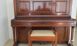 This beautiful dark polished timber upright piano has