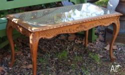 This is a carved French style oak coffee table with a