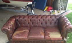 Brown leather chesterfield lounge. Condition is worn