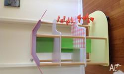A large colourful three tiered dollshouse made from