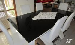 Modern glass top dining table with six leather chairs.