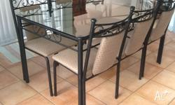 Stylish glass top dining table set on wrought iron base