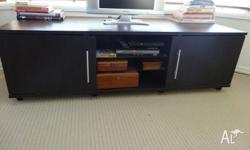 Lowset brown entertainment unit on wheels. 2 doors on