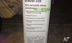 Black fold away travel cot, in its own carry bag and