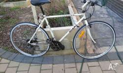 Older hybrid bike with new white wall tyres. 700c