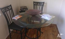 round glass dining table. Has 4 chairs with brown