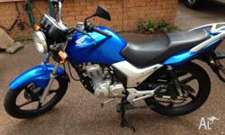 For sale is a blue Honda CB125E motorbike. Near new