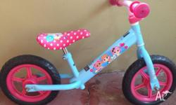 Pink and blue balance bike with adjustable seat. Barely