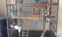 Large bird cage with stand including toys & seeds.