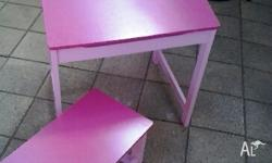 Pink wooden desk that opens for storage, with chair.
