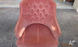 Pink velvet/velour tub chair with fringed bottom.