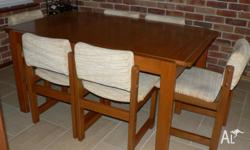 A solid quality timber dining table and six chairs in