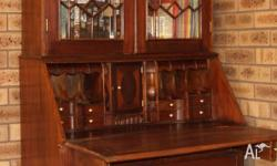 This is a mahogany reproduction bureau bookcase with a