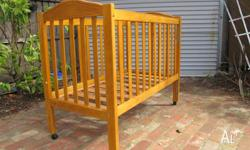 Used solid timber cot with a lacquered timber finish.