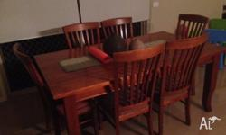 A solid timber dining table and chairs, 7 years old.