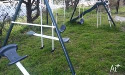 For sale is a swing set with a slide and see saw on
