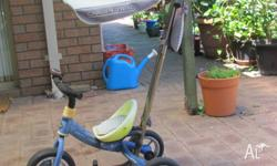 Tricycle with foot rests and push handle for when