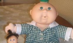 Two cabbage patch dolls.. One is a normal sized doll,