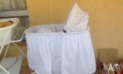 White baby bassinet, on stand with wheels. Hardly used.