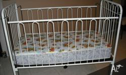 A baby cot with white metal frames in great condition