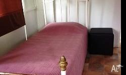 White tubular bed with brass and ceramic bed ends