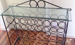 Wrought iron wine rack with glass top/shelf. Holds 40