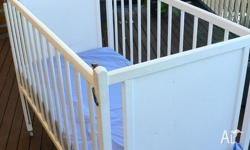baby cot, white. has a single rail drop. has wheels, so