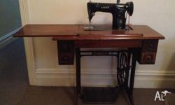 wooden brown treddle singer sewing machine in working