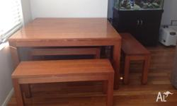 Square solid wooden dining table with four bench seats